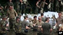 2013年6月,在位于德国东部马格德堡市艾尔比河,德国联邦国防军士兵和其他人一起堆沙袋。