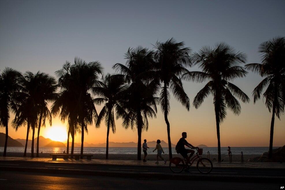 Người dân tập thể dục dọc theo bãi biển Copacabana vào lúc mặt trời mọc tại Rio de Janeiro, Brazil.