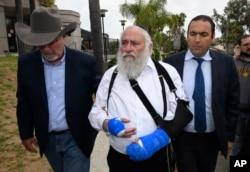 ຣາບາຍ ຢິສໂຣແອລ ໂກລສຕີນ (Rabbi Yisroel Goldstein) ກາງ ຜູ້ທີ່ໄດ້ຮັບບາດເຈັບ, ເດີນທາງມາຮອດ ກອງປະຊຸມຖະແຫລງຂ່າວ ຢູ່ທີ່ ວັດຊາວຢິວ ຊາບາດ ຂອງເມືອງໂພເວ (Chabad of Poway synagogue), ວັນທີ 28 ເມສາ 2019, in Poway, California.