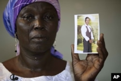 FILE - Martha Mark, the mother of kidnapped school girl Monica Mark cries as she displays her photo, in the family house, in Chibok, Nigeria.