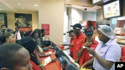 Customers wait to place their orders at a Kentucky Fried Chicken [KFC] restaurant at the Nakumat junction in Nairobi, Kenya, August 23, 2011.