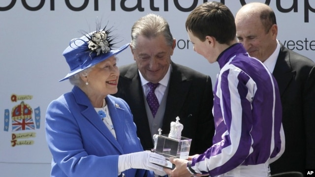 Britain's Queen Elizabeth II presents the trophy to the winning jockey of the Diamond Jubilee Coronation Cup race, June 2, 2012