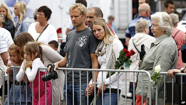 People at Oslo Cathedral pay their respects to victims of last week's bomb attack and shootings in Norway, July 27, 2011