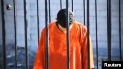Um homem que se acredita ser o piloto jordano Muath al-Kasaesbeh dentro de uma gaiola regado com gasolina.