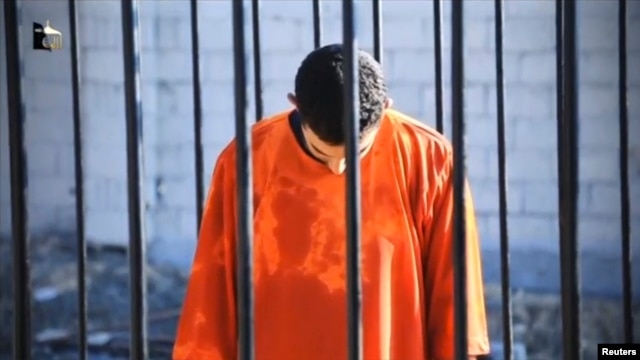 A man purported to be Islamic State captive Jordanian pilot Muath al-Kasaesbeh is seen standing in a cage in this still image from an undated video filmed at an undisclosed location made available on social media on Feb. 3, 2015.