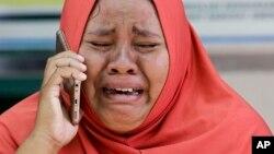 Seorang ibu menangis karena tidak bisa melihat jasad putrinya yang telah dikubur massal.