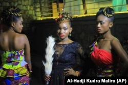 In this photo taken Saturday Dec. 23, 2017, Models pose for a photograph back stage before a fashion show in Beni Eastern Congo .