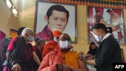 A health worker inoculates a dose of a COVID-19 coronavirus vaccine to a Buddhist monk