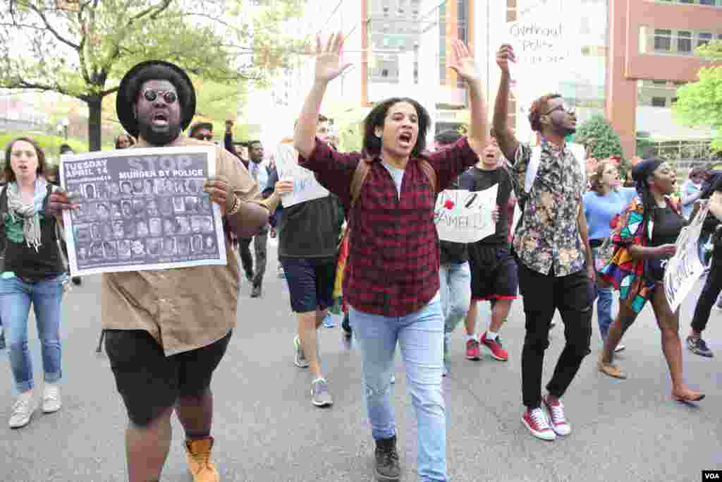 Baltimore students hold their hands up symbolically in a massive march against police brutality and discrimination. April 30, 2015. (Victoria Macchi/VOA News)