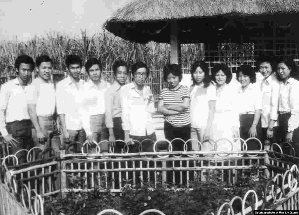 ក្នុងរូបថតសខ្មៅនេះ លោក គួជ មាលីវ (កណ្តាលពីខាងឆ្វេង) ថតរូបជាមួយជនភៀសខ្លួនខ្មែរមួយក្រុមដែលបានរៀនភាសាអង់គ្លេសពីរូបលោក នៅក្នុងឱកាសប្រារព្ធពិធីចូលឆ្នាំថ្មីតាមប្រតិទិនច័ន្ទគតិ នៅជំរំ Minh Tan 1 ប្រទេសវៀតណាម កាលពីឆ្នាំ ១៩៨៥។ ជនភៀសខ្លួនភាគច្រើននៅជំរំនេះ រួមទាំងលោក គួជ មាលីវ ផង គឺជាពលរដ្ឋខ្មែរកាត់ចិន។ (រូបថតផ្តល់ឲ្យដោយលោក គួជ មាលីវ)