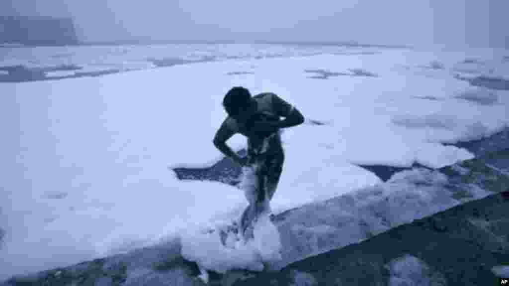 A man cleans foam from his body after taking a bath in the polluted waters of river Yamuna on a cold winter morning in New Delhi January 19, 2012.
