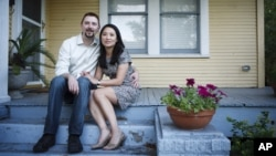 FILE - Hai Nguyen, 37 and her husband Jon Pope, 37, sit outside their home in Houston.