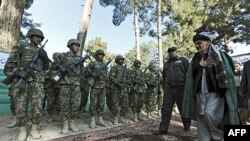 Ashraf Ghani Ahmadzai (R), head of the Transition Commission, inspects an Afghan military guard during a ceremony to hand over security control in Qala Naw, center of Badghis province. (file)