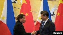 2016年10月20日,菲律宾总统杜特尔特(左)与中国主席习近平在北京举行的一场签字仪式后握手。