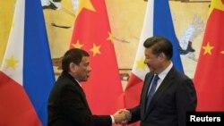រូបឯកសារ៖ លោក Rodrigo Duterte (ឆ្វេង) ប្រធានាធិបតីប្រទេសហ្វីលីពីនចាប់ដៃជាមួយនឹងលោក Xi Jingping ប្រធានាធិបតីប្រទេសចិន នៅទីក្រុងប៉េកាំង ប្រទេសចិន កាលពីថ្ងៃទី២០ ខែតុលា ឆ្នាំ២០១៦។