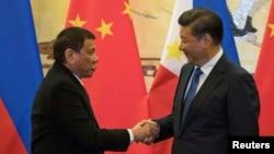 Presiden Filipina Rodrigo Duterte(kiri) dan Presiden China Xi Jinping berjabat tangan dalam pertemuan di Beijing, China, Kamis (20/10).