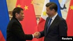 Tổng thống Philippines Rodrigo Duterte (trái) bắt tay Chủ tịch Trung Quốc Tập Cận Bình sau một lễ ký kết ở Bắc Kinh, Trung Quốc, 20/10/2016.
