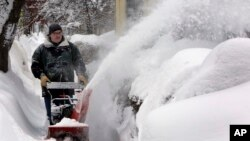 FILE - A man clears snow in Concord, N.H. Foul weather in parts of the United States has snarled transportation and slowed some business operations.