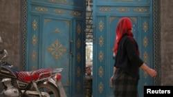 中國新疆一名維吾爾族女子走過一扇門,一個孩子正在向外張望。(2013年10月31日)