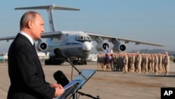 FILE - Russian President Vladimir Putin addresses the troops at the Hemeimeem air base in Syria, Dec. 11, 2017.