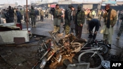 Pakistani security officials examine the site of a suicide bomb attack on the outskirts of Peshawar, Jan. 19, 2016. At least 12 people were killed in a suicide attack on a market during morning rush hour in the outskirts of the northwestern city, official