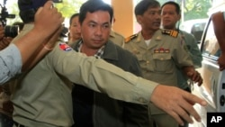 Chay Sarith, center, a suspected attacker who is accused of beating two opposition lawmakers along with two others, is escorted by police officers at Phnom Penh Municipal Court in Phnom Penh, Cambodia, Wednesday, Nov. 4, 2015.