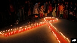 FILE - Nepalese women and children light candles on the eve of World AIDS Day in Kathmandu, Nepal, Nov. 30, 2015.