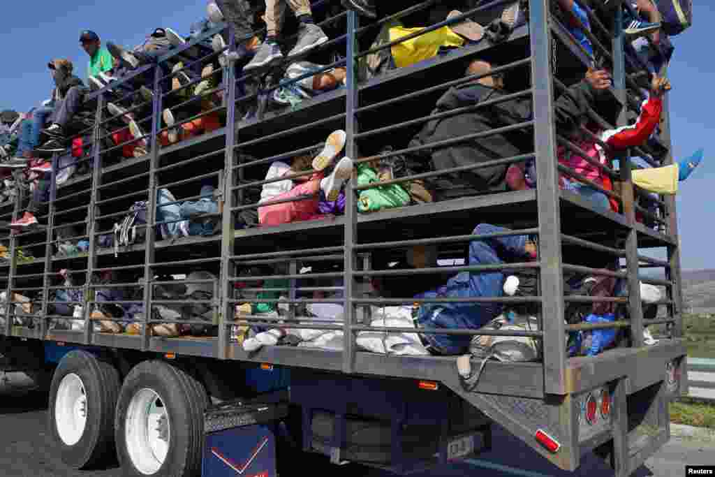 Migrants, part of a caravan of thousands traveling from Central America en route to the United States, travel inside a chicken truck as they make their way to Irapuato from Queretaro, Mexico, Nov. 11, 2018.