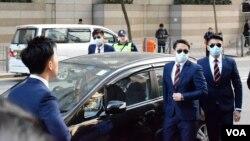 多名被告步入法庭前戴墨鏡及口罩。(美國之音湯惠芸攝)