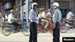 In this photo taken on Nov. 2, 2002, Cambodian police redirect traffic in Phnom Penh, Cambodia.
