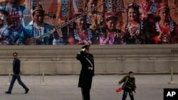 2013年11月9日,在中共召开18届三中全会期间,一名拿着中国国旗的小男孩在天安门广场跑过执勤武警身边,背后是宣传新疆人民的展览。