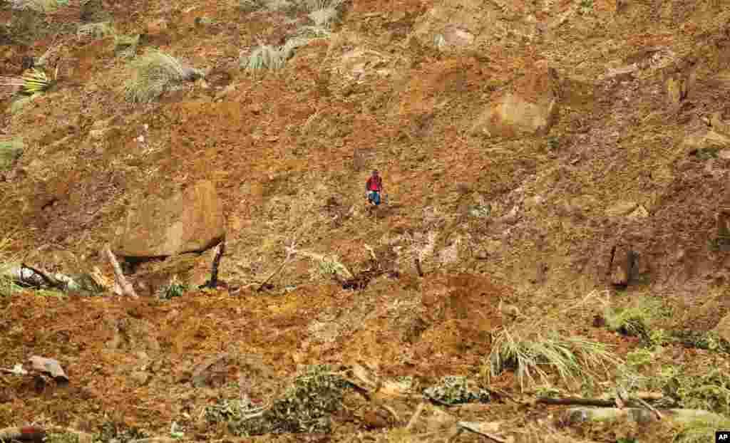 A Sri Lankan man navigates his way through mud and sludge caused by a mudslide at the Koslanda tea plantation in the Badulla district, about 220 kilometers east of Colombo, Sri Lanka, Oct. 30, 2014.