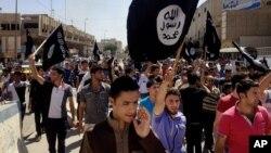 지난 2014년 6월 이슬람 극단주의 무장단체 ISIL이 점령한 이라크 모술에서, ISIL 지지자들이 ISIL 깃발을 들고 행진하고 있다. (자료사진)