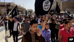 FILE - Demonstrators chant pro-Islamic State group slogans as they carry the group's flags in front of the provincial government headquarters in Mosul, Iraq, June 16, 2014.
