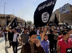 FILE - In this June 16, 2014, file photo, demonstrators chant pro-Islamic State group slogans as they carry the group's flags in front of the provincial government headquarters in Mosul, Iraq.