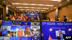 PM India Narendra Modi (tengah, di layar kiri) berbicara dengan PM Vietnam Nguyen Xuan Phuc (layar kanan) pada KTT ASEAN-India yang diadakan secara virtual karena pandemi Covid-19 di Hanoi, 12 November 2020. (Foto: Nhac NGUYEN / AFP)