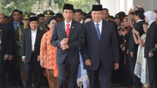 Indonesia's President Joko Widodo, left, walks with former president Susilo Bambang Yudhoyono at the presidential palace in Jakarta, Indonesia, Oct. 20, 2014.