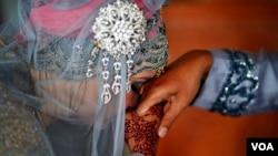 Seorang perempuan mencium tangan suaminya setelah akad nikah di sebuah masjid di Banda Aceh, 9 Desember 2012. (Foto: Reuters)