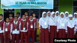 Siswa-siswi SD Al Bina Masohi, Maluku, berfoto dengan spanduk yang menyemangati mereka saat menikuti Ujian Sekolah Berstandar Nasional (UASBN) 2019. (Courtesy: Darno Yusuf Mulyono/SD Al Bina Masohi)