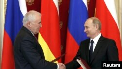 Russian President Vladimir Putin (R) shakes hands with President of the Georgian breakaway region of South Ossetia Leonid Tibilov during a signing ceremony in Moscow, (March 18, 2015.)