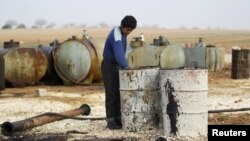 FILE - A youth works at a makeshift oil refinery in the countryside south of Idlib, Syria.