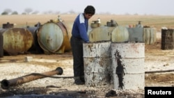 FILE - The Islamic State is funded, in part, through oil. Here, a youth works at a makeshift oil refinery in Syria that, according to its owner, gets the crude oil from Islamic State-controlled areas of Syria and Iraq.