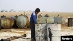 FILE - A youth works at a makeshift oil refinery in Syria that, according to its owner, gets the crude oil from Islamic State-controlled areas.