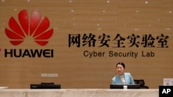 FILE - A receptionist stands at the front counter of the Huawei's Cyber Security Lab at the Huawei factory in Dongguan, China's Guangdong province, March 6, 2019.