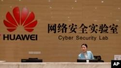 ພະນັກງານຕ້ອນຮັບ ຢືນຢູ່ພາຍໃນໂຕະ ຂອງຫ້ອງທົດລອງ ທາງດ້ານຄວາມປອດໄພທາງໄຊເບີ ຂອງບໍລິສັດຫົວເຫວ Huawei ຢູ່ໂຮງງານ ຂອງຫົວເຫວ ໃນເມືອງ ດົງກວງ ແຂວງກວງດົງ ຂອງຈີນ, ວັນທີ 6 ມີນາ 2019.