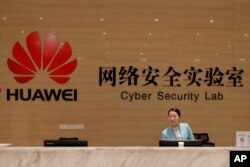 FILE - A receptionist stands at the front counter of Huawei's Cyber Security Lab at the Huawei factory in Dongguan, China's Guangdong province, March 6, 2019.