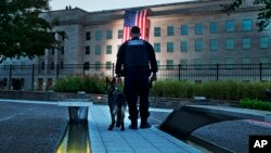 At the Pentagon Memorial, a K-9 officer pauses as he looks toward the U.S. flag as it is draped on the side of the Pentagon where the building was attacked on September 11 in 2001, on the 14th anniversary of the attack, Sept. 11, 2015, outside Washington.