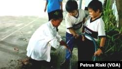 Siswa-siswi dari Madrasah Ibtidaiyah (MI) Islamiyyah-Plosogenuk, sedang mengambil air wudu sementara siswa siswi SD Kristen Petra membantu dengan memegangi selang air (Foto:VOA/Petrus Riski).