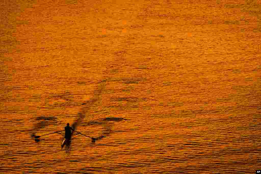 A lone boater skims across the surface of the Potomac River at sunset in Washington, D.C., USA, Oct. 8, 2013.