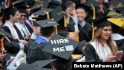 "FILE - A graduating student wears a cap reading ""hire me,"" as the City College of New York (CCNY) class of 2016 assemble for commencement, Friday June 3, 2016, in New York."